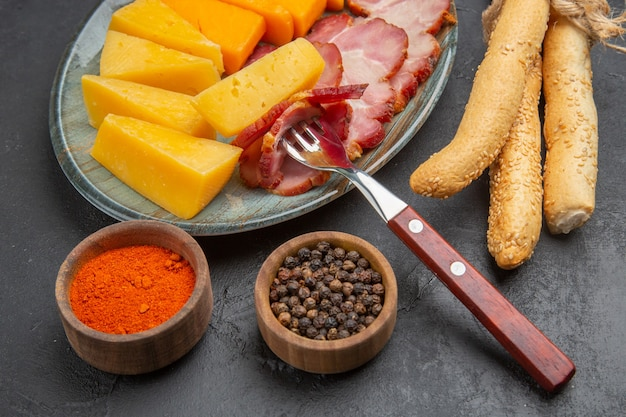 어두운 배경에 파란색 접시 고추에 맛있는 소시지와 치즈 조각의 오버 헤드보기