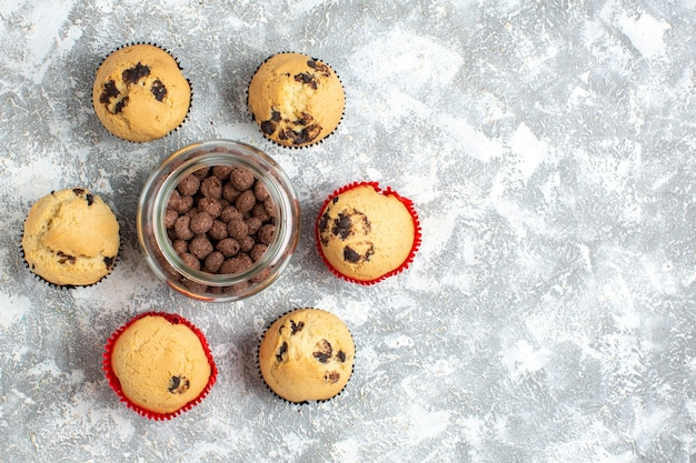 氷のテーブルの右側にあるガラスの鍋においしい小さなカップケーキとチョコレートの俯瞰図