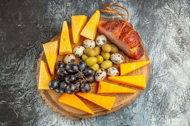 灰色の背景の茶色のトレイに果物やワインの食べ物を含むおいしいスナックの俯瞰図