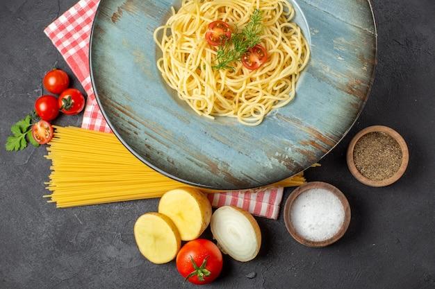 Вид сверху вкусных спагетти, подаваемых с помидорами, зеленью и разными специями, сырыми макаронами на красном полосатом полотенце на черном столе