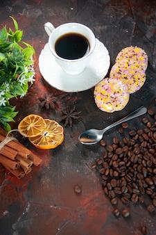 Вид сверху на вкусное сахарное печенье и чашку кофе, цветочный горшок, сушеные лимоны, ломтики корицы, бобы на темном фоне цветов