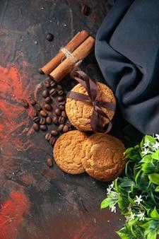 Вид сверху вкусного сахарного печенья и кофейных зерен цветочный горшок полотенце с корицей и лаймом на фоне темных цветов