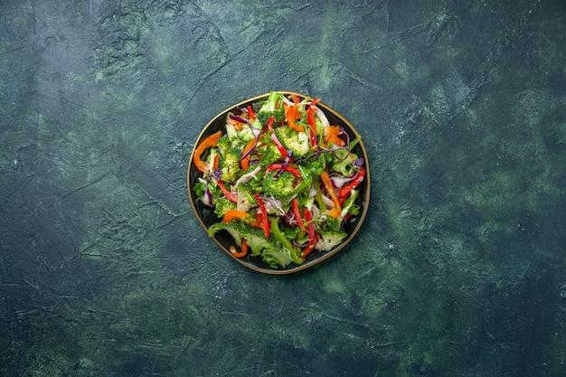 暗い背景にさまざまな新鮮な野菜とプレートのおいしいビーガンサラダの俯瞰図