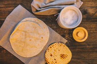 Overhead view of delicious wheat mexican tortilla on table with jar of sugar