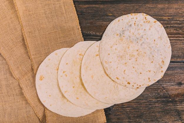 Вид сверху вкусной пшеничной мексиканской лепешки на столе