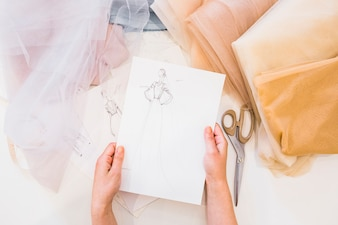 Overhead view of designer's hand holding fashion sketch over workdesk