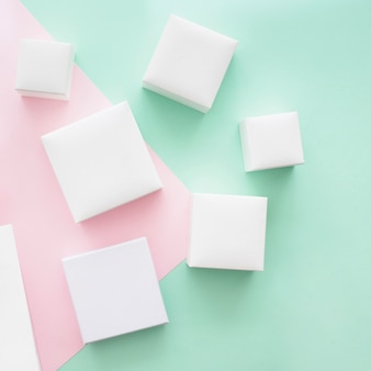 Overhead view of different white boxes on green and pink paper backdrop