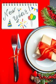 Вид сверху на обеденные тарелки с подарком и еловые ветки, набор столовых приборов, украшение, аксессуар, хвойная шишка, следующая записная книжка с новогодним письмом и рисунками на красной салфетке