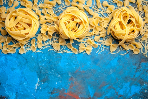 青い背景にパスタ ヌードルを一列に並べた夕食の準備の俯瞰