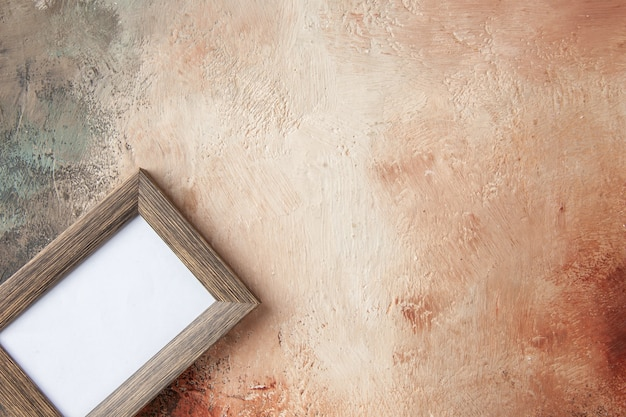 空きスペースのあるミックスカラーの壁に掛けられた空のフォトフレームの俯瞰図