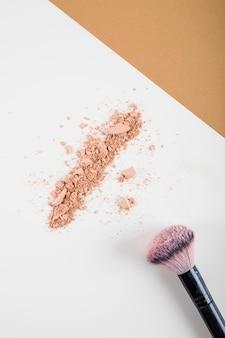 Верхний вид лицевого порошка и кисти на двухцветном фоне