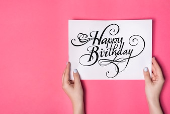 Overhead view of female's hand holding happy birthday card against pink background