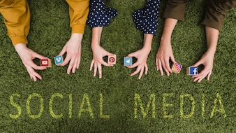 Overhead view of female's hand holding social network app symbol blocks on lawn