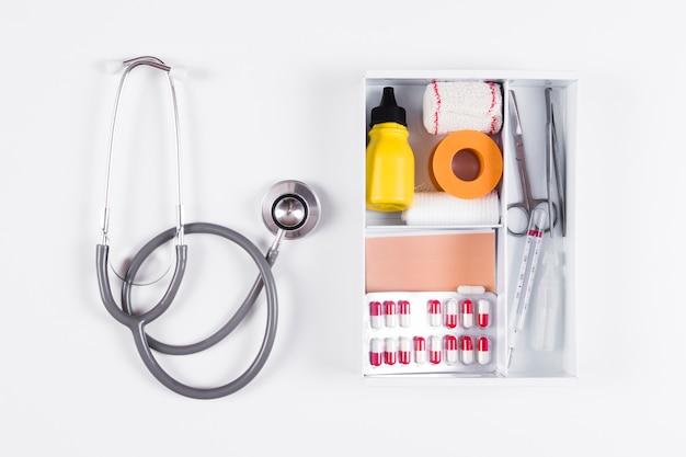 Вид сверху аптечки и стетоскоп на белом фоне