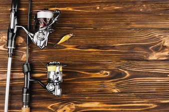 Overhead view of fishing rod and bait on wooden background