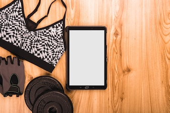 Overhead view of Fitness equipments and digital tablet on wooden floor