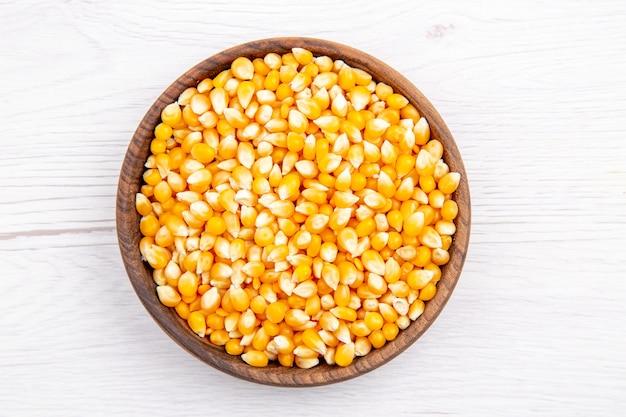 Вид сверху свежих зерен кукурузы в коричневой миске на белом фоне