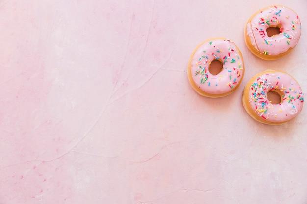 ピンクの背景に散水と新鮮なドーナツのオーバーヘッドビュー