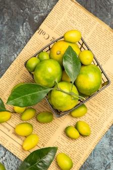 灰色の背景ストックイメージの新聞の黒いバスケットに新鮮なキンカンとレモンの俯瞰図