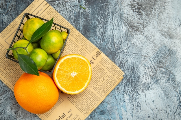 灰色の背景に新聞のバスケットの内側と外側の新鮮なレモンの俯瞰図