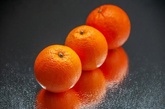 여유 공간이 있는 검정색 배경에 나란히 서 있는 신선한 오렌지의 오버 헤드 보기