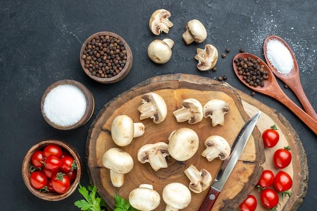 Вид сверху свежих сырых грибов и специй из помидоров на деревянной доске на черном фоне