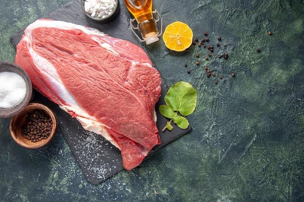 Вид сверху свежего сырого красного мяса на черном подносе, бутылка с перцем и упавшим лимонным маслом на темном фоне
