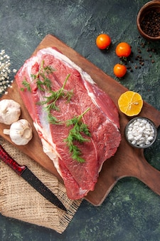 新鮮な生の赤身の肉の俯瞰図緑のニンニクレモン塩茶色の木製まな板ナイフヌードカラータオルトマトコショウ暗い色の背景