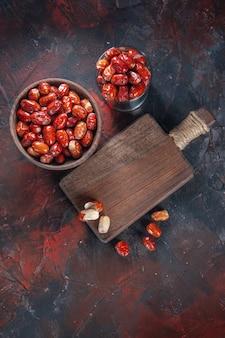 Вид сверху свежих сырых плодов малины в мисках и на деревянной разделочной доске на фоне смешанных цветов