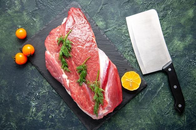 まな板の上の新鮮な赤生肉緑レモンスライスと緑黒ミックスカラー背景のトマト斧の俯瞰図