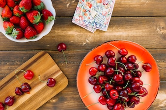 Overhead view of fresh red strawberries and cherries on wooden plank