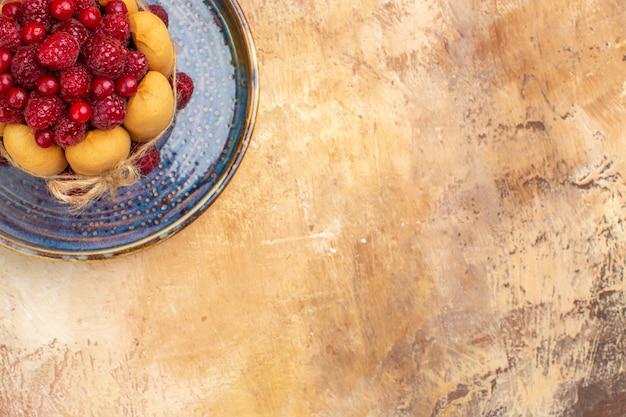 混合色のテーブルにフルーツと焼きたてのギフトケーキの俯瞰図