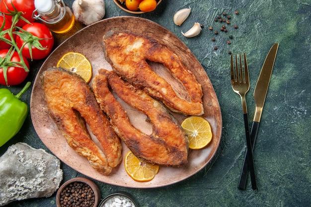 茶色のプレートに揚げた魚とレモンスライスの俯瞰図スパイストマトオイルボトルのミックスカラーテーブルに空きスペースがあります