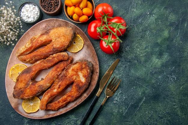 Вид сверху жареной рыбы и ломтиков лимона на коричневой тарелке, томатов, кумкватов на столе смешанных цветов со свободным пространством
