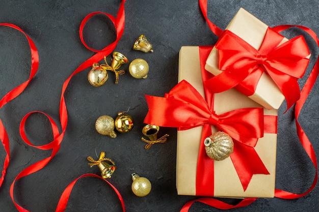 Вид сверху подарочной коробки с красной лентой и декоративными аксессуарами на темном фоне