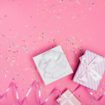Overhead view of gift boxes with curl ribbon and sprinkle on pink background