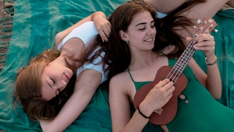 Overhead view of girl lying over her friends playing ukulele at beach