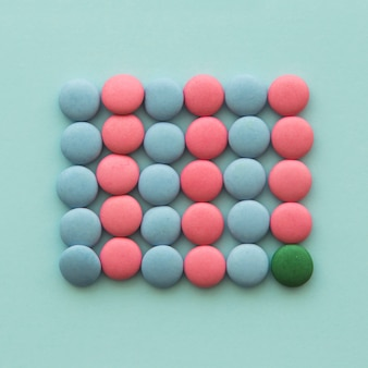 Overhead view of green candy with pink and blue candies