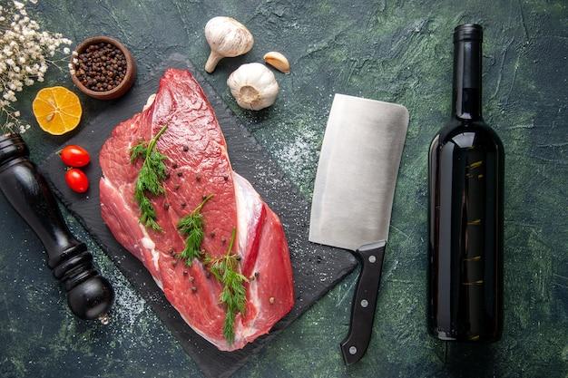 커팅 보드에 있는 신선한 붉은 생고기 위에 있는 녹색의 오버헤드 뷰와 녹색 검정 혼합 색상 배경에 후추 레몬 블랙 망치 꽃 와인 병