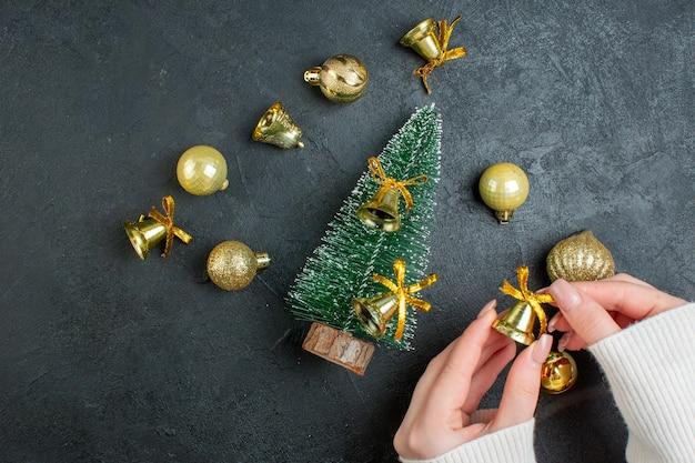 Вид сверху на руку, держащую украшения, подарочные коробки и елку на темном фоне