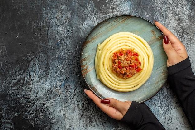 파란색 접시에 맛있는 파스타 식사를 들고 있는 손의 머리 위 전망은 얼음 배경의 왼쪽에서 저녁 식사로 토마토와 고기와 함께 제공됩니다.
