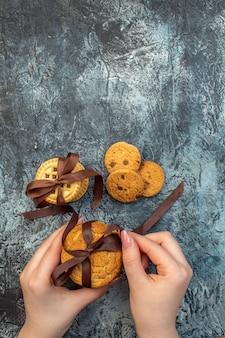여유 공간이 있는 얼음 배경에 맛있는 집에서 만든 쿠키를 들고 있는 손의 오버헤드 보기