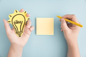 Overhead view of hand holding idea bulb writing with yellow crayon on sticky note over the gray background