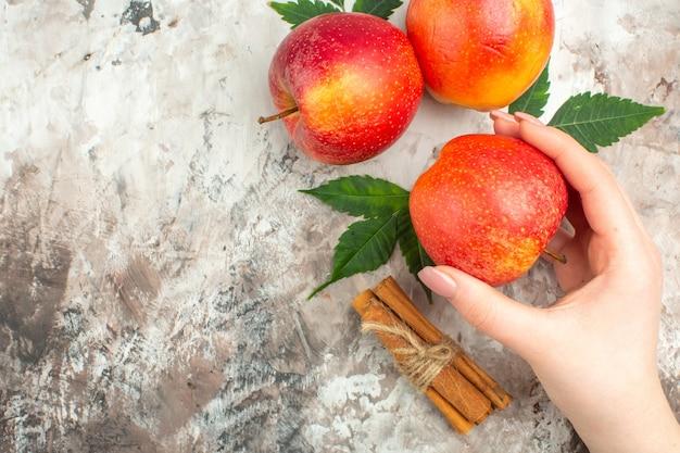 혼합 색상 배경에 신선한 천연 빨간 사과와 계피 라임 중 하나를 들고 있는 손의 머리 위