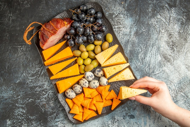 氷の背景の上の茶色のトレイにワインのためのおいしい最高のおやつから食品の1つを取る手の俯瞰図