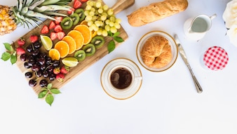 Overhead view of healthy breakfast with fruit assortment, tea and bread