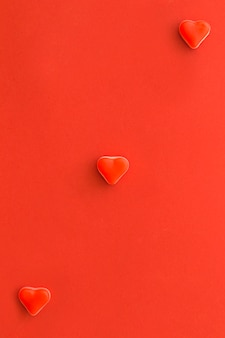 Overhead view of heart shape candies on red surface