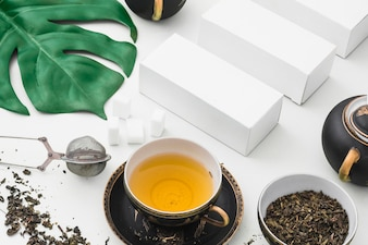 Overhead view of herbal tea with sugar cubes and white boxes on backdrop