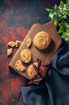 Вид сверху на домашнее вкусное сахарное печенье на деревянной доске и цветочный горшок на фоне темных цветов