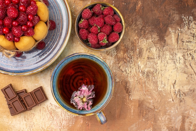 Вид сверху на мягкий торт горячего травяного чая с фруктами и шоколадными батончиками на столе смешанных цветов